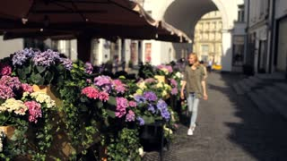 beautiful woman walking around the city along a cafe with flowers