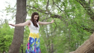 Beautiful Young Girl Balances Standing on a Tree