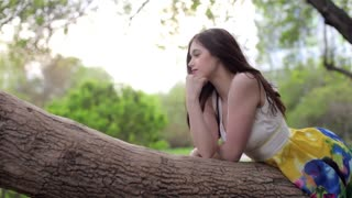 Beautiful Young Girl Resting Lying on a Tree in the Park