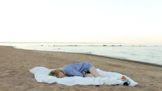 Beautiful Young Woman Wakes up on the Beach. Girl in Pajamas Sleeping on a Blanket on the Beach