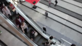 Blurred People on an Escalator in the Business Center