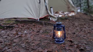 burning kerosene lamp on the background of a tent in the forest