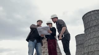 Business People in Helmet, Engineers Examines Blueprints on Background of Nuclear Power Plant