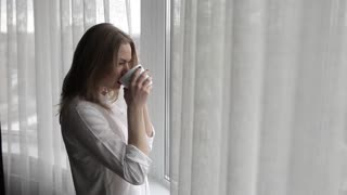 Business Woman Drinking Coffee by the Window