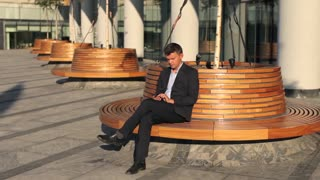 businessman on break resting with phone on a bench near modern office building