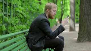 Businessman Sitting in a Park on a Bench and Writing a Message on the Phone