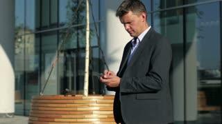 businessman using smart phone near the office