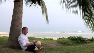 businessman with a coconut and a tablet sits under a palm tree on the beach