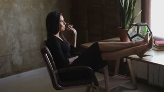 charming Business Woman with legs on table in a stylish office