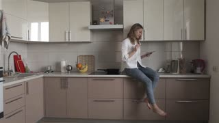 Cheerful Woman is Sitting in the Kitchen With a Tablet, Business at Home