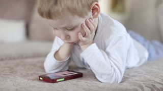 Child Watching Video, Playing on Phone Lying on Sofa