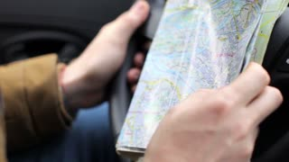 close-up, a man holding a map and driving a car