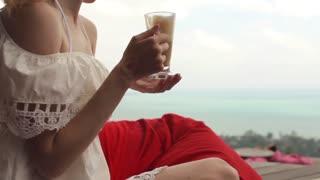 close-up. girl drinks smoothies in cafe with sea views