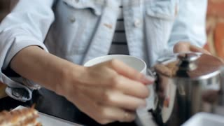Close-Up. Girl Pours Green Tea in a Mug