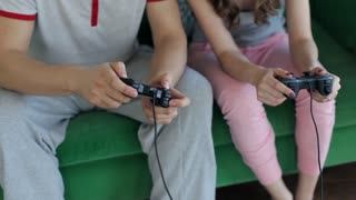 Close-Up, Man and Woman Play Joysticks in the Console