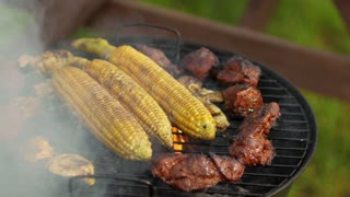 corn and meat roasted on grill fire