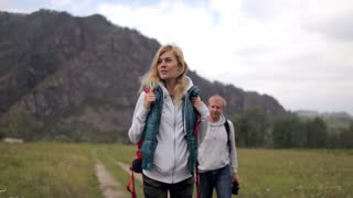 couple of travelers with a map among the mountains. look through binoculars