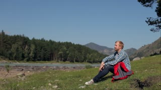couple travelers Relaxing on a Field in the background of the mountains