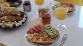 delicious breakfast of scrambled eggs, fruits and croissants