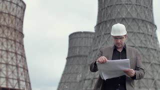 Engineer in Helmet, Supervisor Examines Blueprints on Background of Nuclear Power Plant