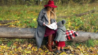 fashionable mother with her daughter reading a children's book in the autumn park