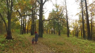 fashionable woman and daughter are walking in the autumn park