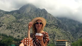 fashionable woman in a dress eating raspberries on a background of mountains