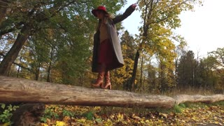 fashionable woman walking on a log in an autumn park