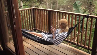 female lies in a hammock with phone lies in a hammock on the terrace