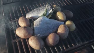 fish with potatoes cook on the grill