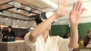 Girl in Virtual Reality Glasses in a Cafe