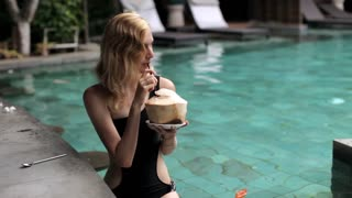 girl is drinking coconut at the pool bar