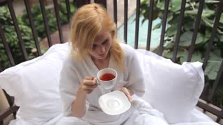 girl is drinking tea in bed in the tropics
