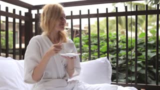 girl is drinking tea in bed on the terrace of a tropical hotel