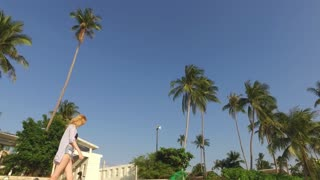 girl is walking along a tropical beach among palm trees