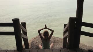 girl practicing yoga on a stony shore
