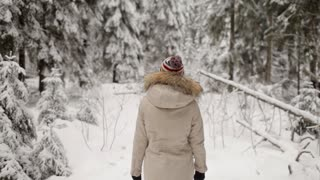 Girl Standing Back in the Winter Forest