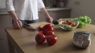 Girl Takes a Tomato and Cuts Into a Salad. Only Hands