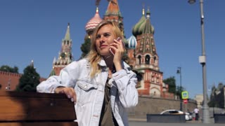 girl talking on the phone sitting in the center of Moscow