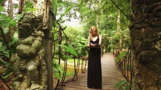 girl tourist with a map walks in the jungle with statues in Asian style