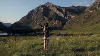 girl traveler enjoys nature in a mountain glade