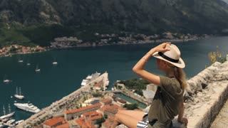 girl traveler sits on a cliff overlooking the old town on the shore of a mountain lake