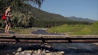 girl traveler with a tablet walking across a bridge across a mountain river