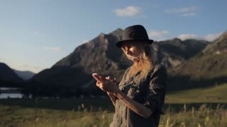 girl traveler with phone writes message among the mountains