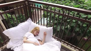 girl wakes up on the terrace in the tropics
