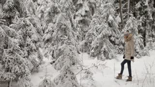 Girl Walks in a Snow-Covered Winter Forest