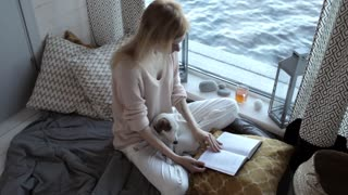 girl with a puppy reading a book sitting by the window with a lake view