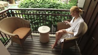 girl with a smartphone sits on the balcony of the hotel and drinks water