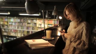 Girl With Phone and Coffee Sitting in a Bookstore Cafe
