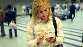 girl writes a message on the phone at a crowded metro station